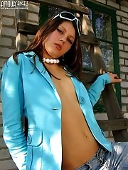 Girl Wearing A Blue Coatee And Jeans On Her Naked Body Flaunts Her Natural Breasts