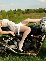 Thrilling Nude Angel Is Sitting On A Big Black Motorbike In White Stockings And Caresses Her Sweet B