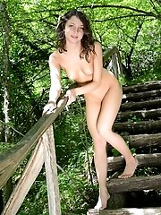 Gorgeous dark haired slim teen cutie posing absolutely naked outdoors near the big tree.